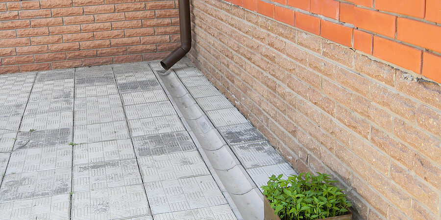 house rain gutter drain pipe with drain tranche on the pavement