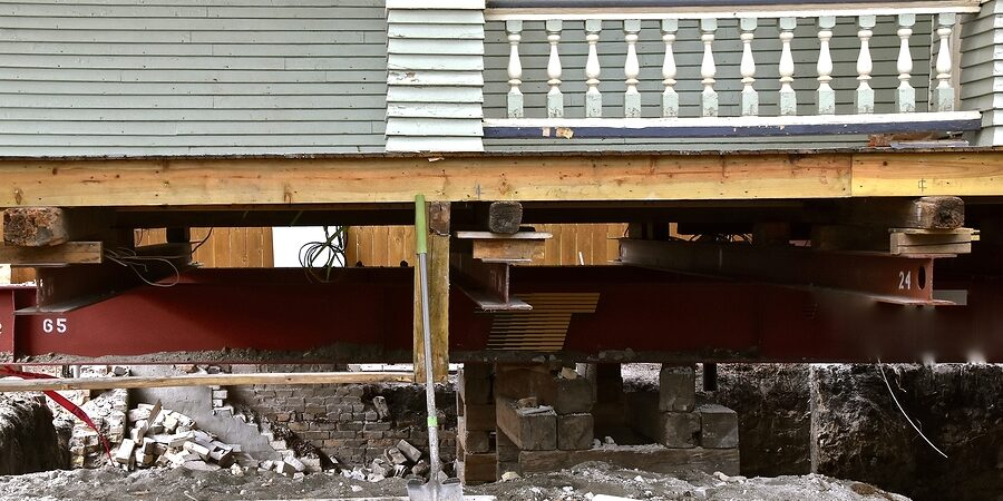 old house rests on steel girders as a new concrete basement and foundation is being created