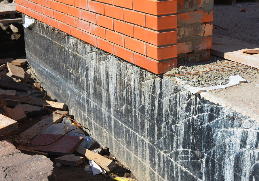 waterproofing house foundation with spray on tar. house insulation waterproofing basement and foundations